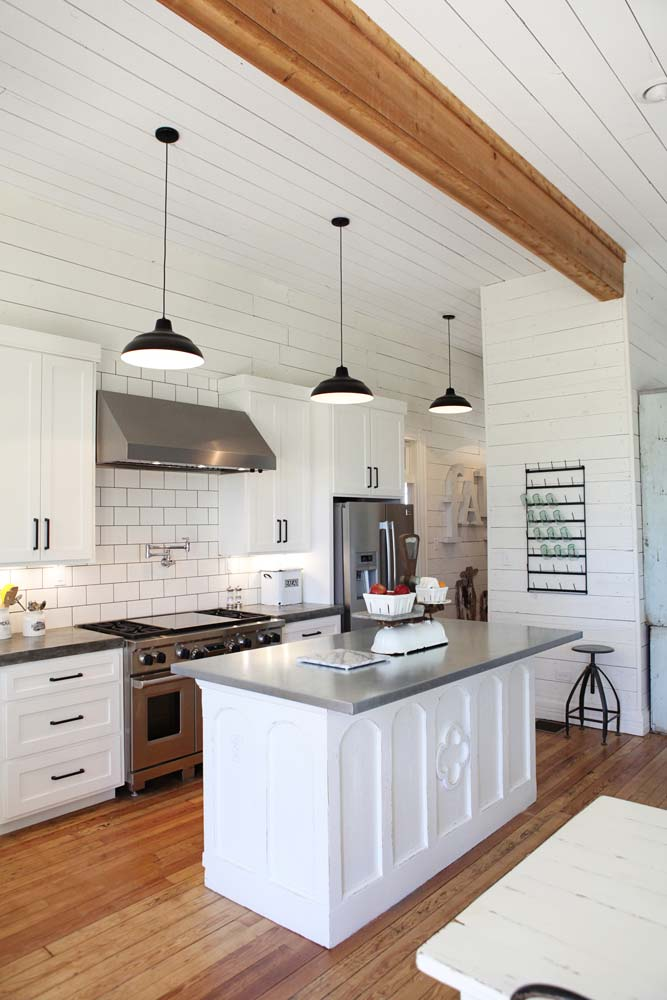 Joanna Gaines white farmhouse kitchen with shiplap walls, natural wood beam, subway tile backsplash, antique island base, and concrete counters.